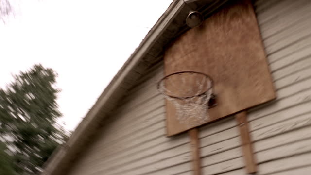 Low angle medium shot basketball being shot at hoop over garage