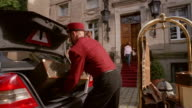 Low angle medium shot bellman loading luggage into trunk of limo as woman looks on / man talking on cell phone