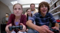 Low angle medium shot boy and girl playing home video game / parents sitting together in background