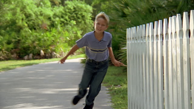 Low angle medium shot boy running stick over white picket fence / Miami, Florida