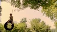 Low angle medium shot boy swinging on tire swing/ Saint-Ferme, France