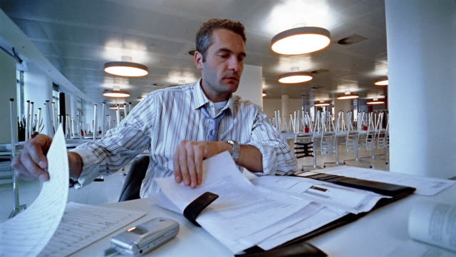 Low angle medium shot businessman sitting alone in lunch room and working / putting head down on table / Berlin