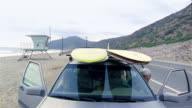 Low angle medium shot car parking at beach / high angle passengers taking surfboards off roof / walking to water