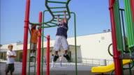 Low angle medium shot children swinging on monkey bars on playground