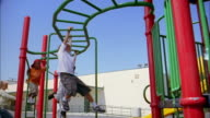 Low angle medium shot children swinging on playground monkey bars
