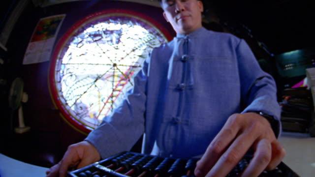 Low angle medium shot Chinese man using abacus