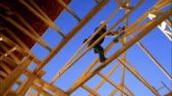 Low angle medium shot construction worker hammering on house frame / blue sky in background / Phoenix, Arizona