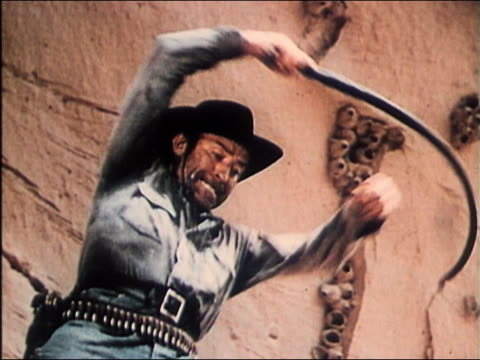 1949 low angle medium shot cowboy (David Kashner) cracking whip in scene from 'The Sundowners'
