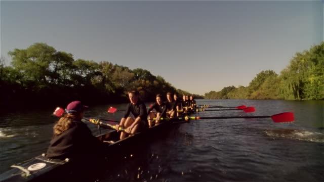 Low angle medium shot crew team rowing racing shell on Charles River