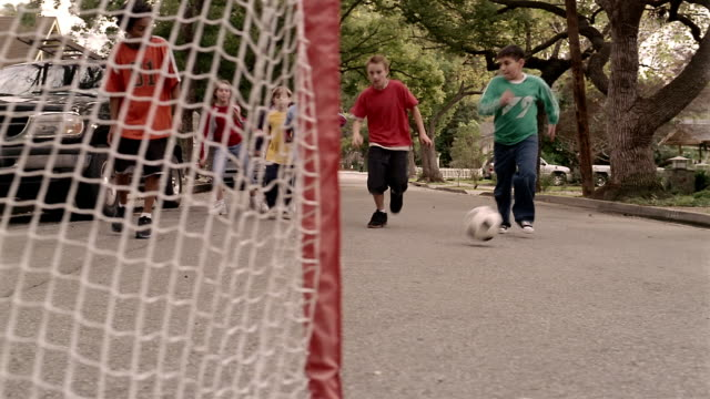 Low angle medium shot dolly shot kids playing soccer in street running towards CAM / boy kicking ball into goal