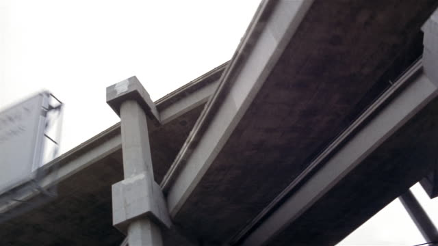 Low angle medium shot dolly shot point of view under I-10 freeway interchange / pan rear point of view traffic on freeway / east of Los Angeles