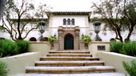 Low angle medium shot exterior of large Spanish-style mansion / Beverly Hills, California