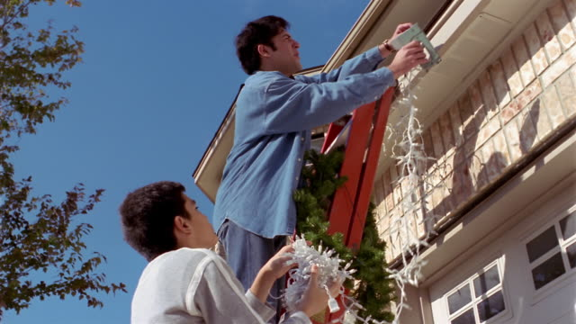 Low angle medium shot father and son on ladder, hanging Christmas decorations on house