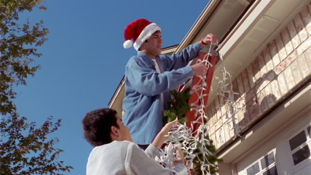 Low angle medium shot father (wearing Santa cap) and son on ladder, hanging Christmas decorations on house