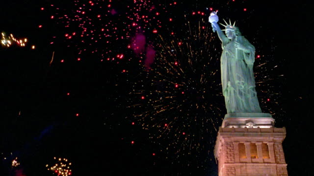 Low angle medium shot fireworks exploding behind Statue of Liberty at night / New York City