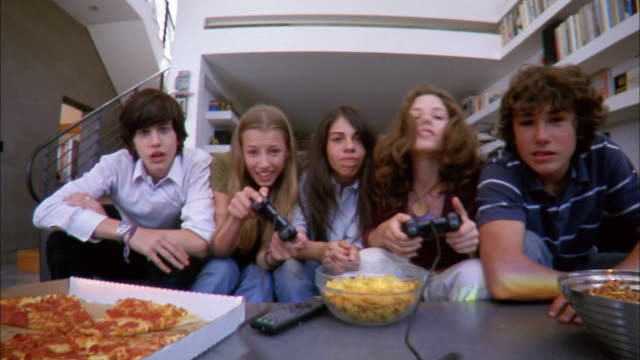 Low angle medium shot five teenagers facing CAM and playing home video games / girl cheering