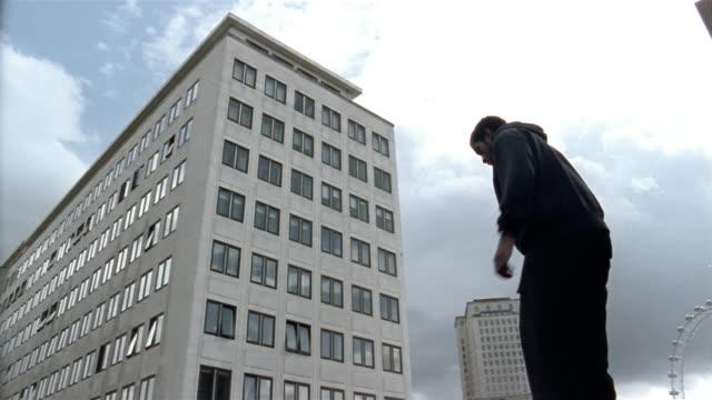 Low angle medium shot freerunner doing back flip on roof w/London Eye in background / London