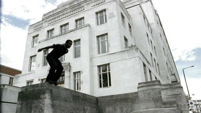 Low angle medium shot freerunner jumping off one ledge and landing on another / flipping onto sidewalk + running off