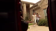 Low angle medium shot kids jumping into van and father closing door with mother in background