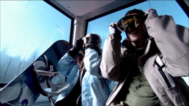 Low angle medium shot male and female snowboarder putting on goggles while riding on gondola / Morzine, France