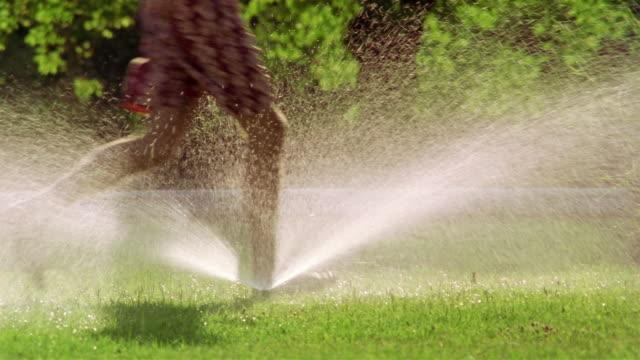 Low angle medium shot man and dog running back + forth through sprinkler / France
