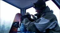 Low angle medium shot man and woman riding gondola / snowboarders helping each other put on goggles / Morzine, France