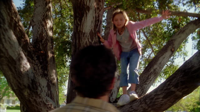Low angle medium shot man helping lift young girl down from tree