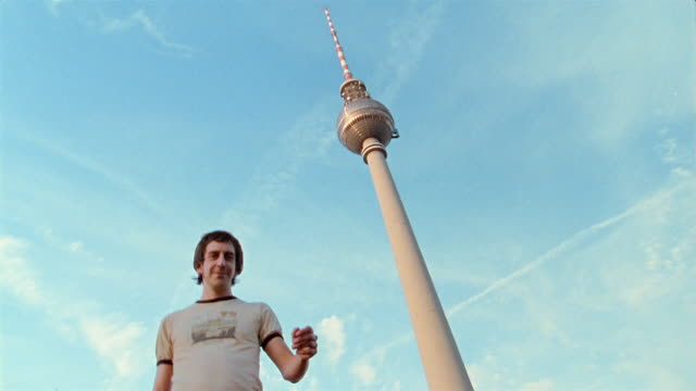 Low angle medium shot man making peace sign with Fernsehturm in background / Berlin, Germany