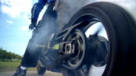 Low angle medium shot man sitting on motorcycle as back wheel spins out / smoke billowing up