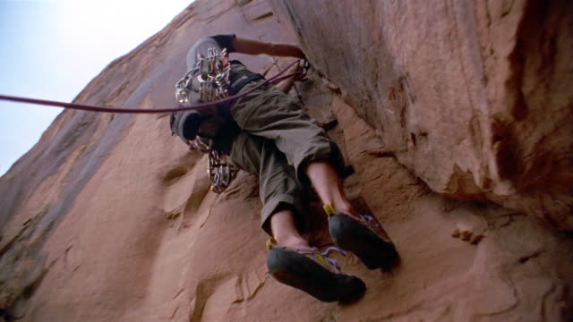 Low angle medium shot man wearing harness and rope climbing rock / securing rope with hooks