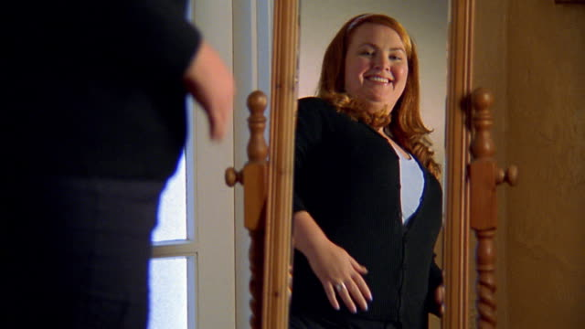 Low angle medium shot overweight woman looking at herself in mirror happily