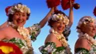 Low angle medium shot pan group of senior women hula dancers / ocean in background