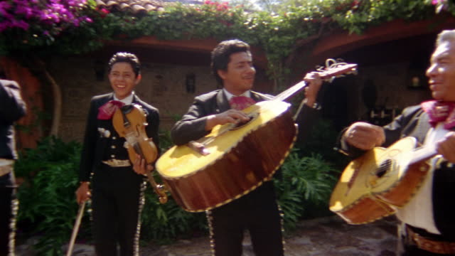 Low angle medium shot pan mariachi band performing in courtyard