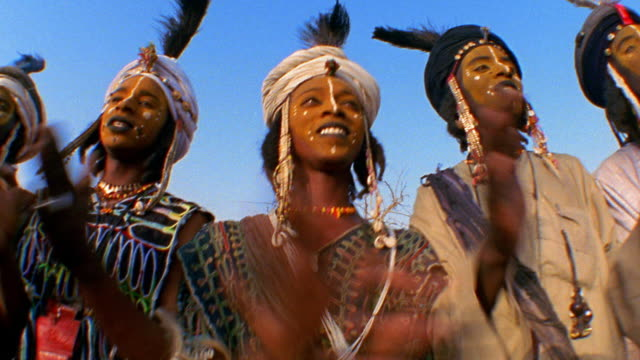 Low angle medium shot pan Wodaabes in tribal dress, face paint and feathered turbans clapping at wedding / Niger