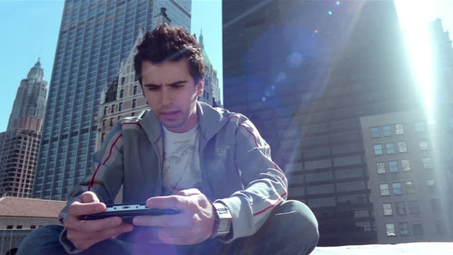 Low angle medium shot pan young man playing handheld video game on sunny day in Manhattan financial district / NYC
