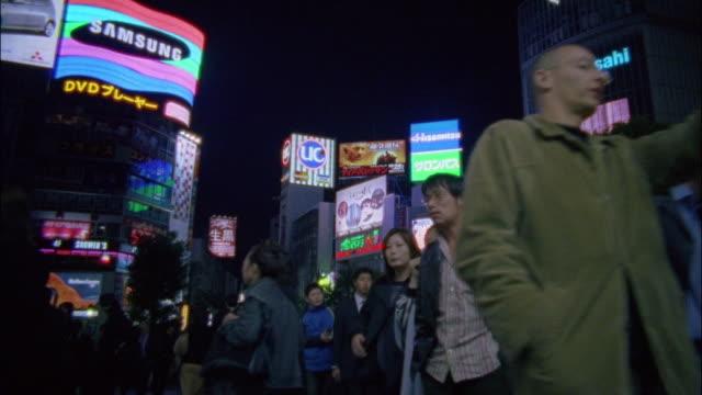 Low angle medium shot pedestrians walking on street / Tokyo, Japan