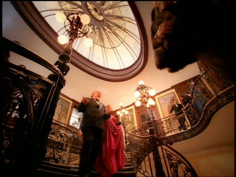 Low angle medium shot people in formalwear descending ornate staircase of theater