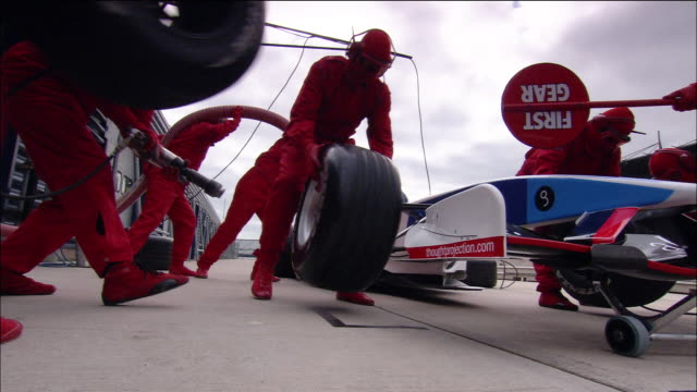 Low angle medium shot pit crew changing tires on Formula One race car during pit stop / car driving off