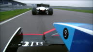 Low angle medium shot point of view over wing of Formula One race car chasing car around track