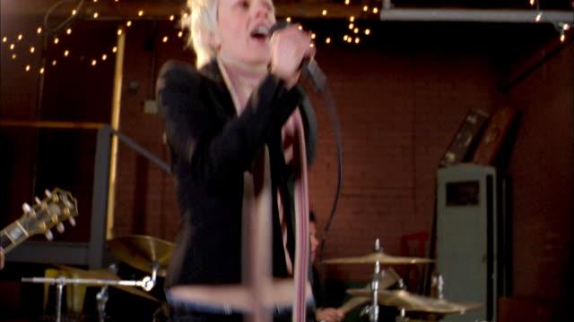 Low angle medium shot punk rock singer jumping and performing w/band