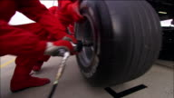 Low angle medium shot rear tire of Formula One race car being changed by pit crew