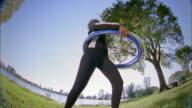 Low angle medium shot senior woman gyrating w/hula hoops