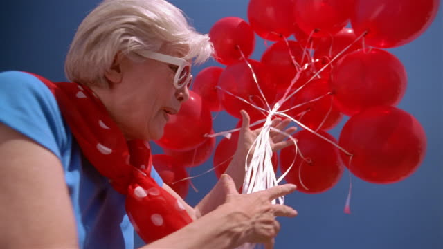 Low angle medium shot senior woman holding red balloons looking down at CAM / releasing balloons into air