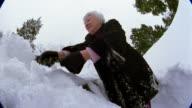 Low angle medium shot senior woman scraping snow off of car / snow falling on CAM