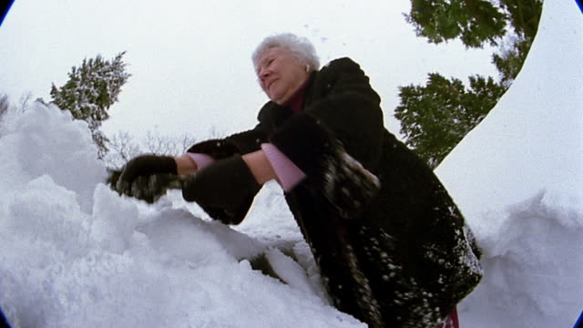 Low angle medium shot senior woman scraping snow off of car / snow falling on CAM