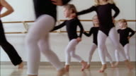 Low angle medium shot teacher leading girls wearing leotards skipping sideways across dance studio during ballet class / one girl straggling behind