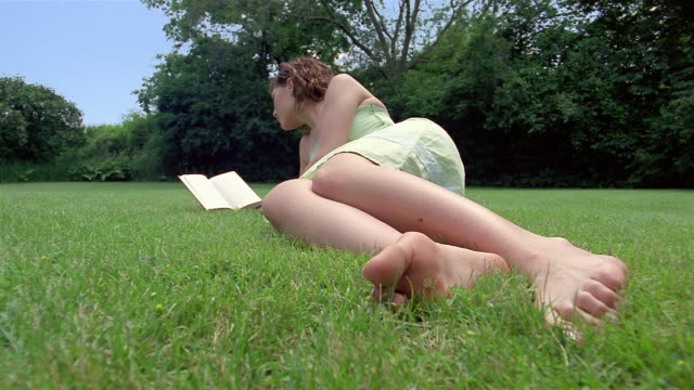 Low angle medium shot teenage girl lying in grass and reading book with trees in background