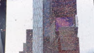 Low angle medium shot tilt down ticker tape falling over Times Square at Broadway and West 45 St. / New York City