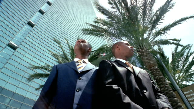 Low angle medium shot tilt up tilt down twin men wearing suits outside skyscraper / looking up and down