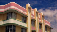 Low angle medium shot time lapse clouds in blue sky over art deco pastel-colored building in Miami / Florida